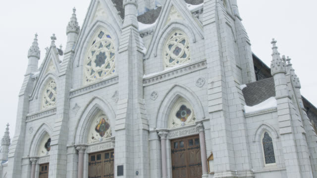 vídeos de stock, filmes e b-roll de medium angle of gothic revival cathedral. three door entrance. stained glass windows and spires visbile. st. mary's basilica in halifax. snow visible. - condado de humboldt califórnia