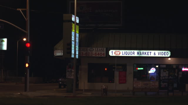 medium angle of liquor store in a strip mall near stoplight and bus stop. 1 stop liquor market and video sign lit. cars drive by. - liquor store stock videos and b-roll footage