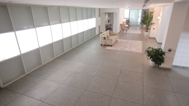 medium angle of lobby or waiting area. could be in hospital or office building. - abwesenheit stock-videos und b-roll-filmmaterial