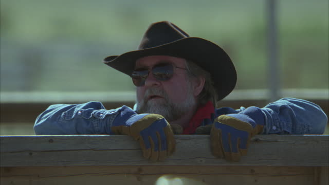 stockvideo's en b-roll-footage met medium angle of man in cowboy hat and sunglasses standing at wooden fence, enclosure, or pen. man wears sunglasses. could be rodeo. - hek