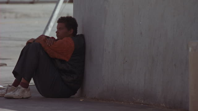 medium angle of man sitting against wall, could be homeless man. - housing difficulties stock videos & royalty-free footage