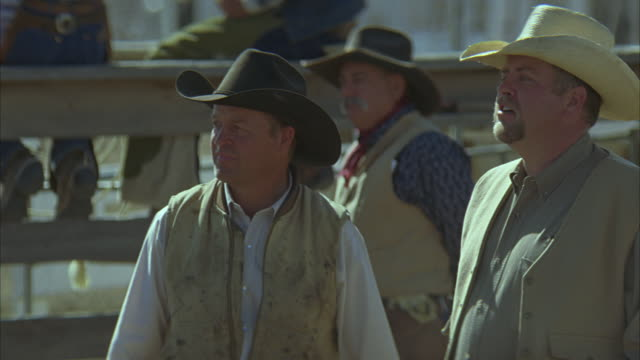 medium angle of men in cowboy hats standing in arena. could be rodeo. - ziegenbart stock-videos und b-roll-filmmaterial