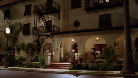 medium angle of multi-story spanish style apartment building. balconies and fire escapes visible on building. fountain and arched entry way visible. cars parked in front of building and pedestrians walk by. could be neighborhood or residential area. cars - spanish culture stock videos & royalty-free footage