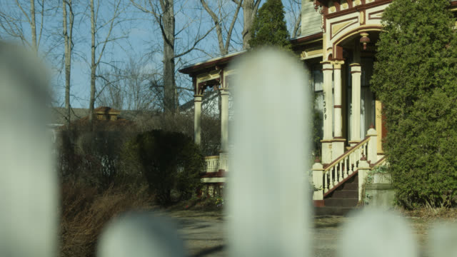 medium angle of multi-story victorian house through fence posts. trees and shrubs visible.