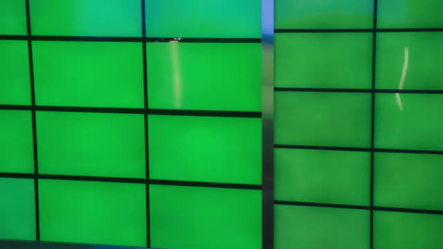 vídeos de stock e filmes b-roll de medium angle of neon green walls or sliding doors. could be television stuido set. - parede
