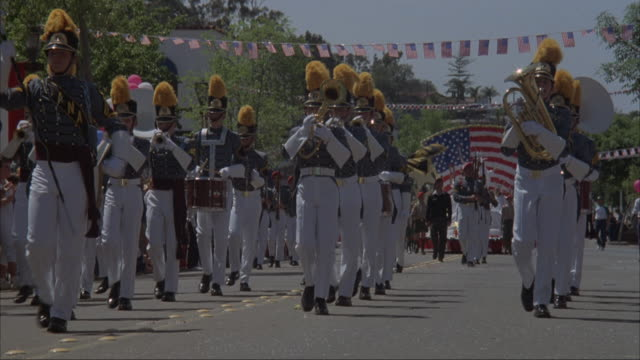 medium angle of parade down city street. see crowd lining sides of road. see clowns, man and women,  military marching band, float with american flag and girls dressed as statues of liberty, and men dressed in colonial dress. probably a fourth of july par - festival float stock videos & royalty-free footage
