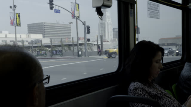 medium angle of passengers on bus, driving through city streets.
