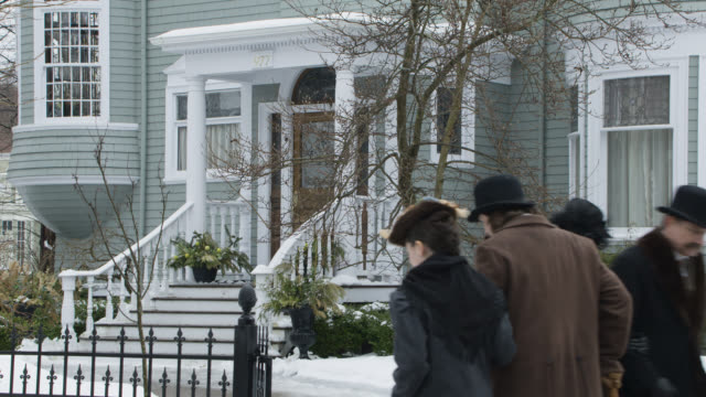 medium angle of pedestrians walking on sidewalk in front of upper class house. snow visible on ground. - arm in arm stock videos & royalty-free footage