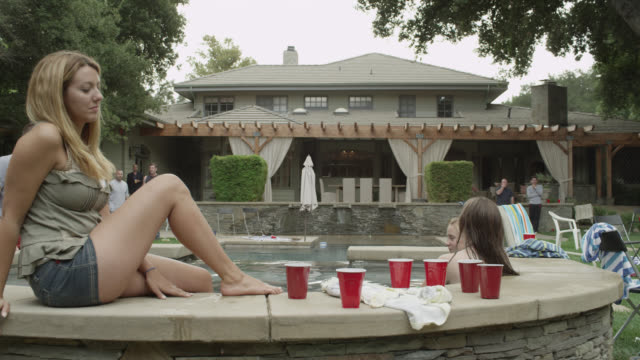 medium angle of people at party in backyard. hot tub or jacuzzi. red cups. two story middle to upper class house.