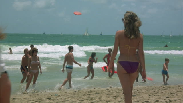 medium angle of people on beach. focus on girl in purple bikini bottom and sunglasses walking toward water. - halbbekleidet stock-videos und b-roll-filmmaterial