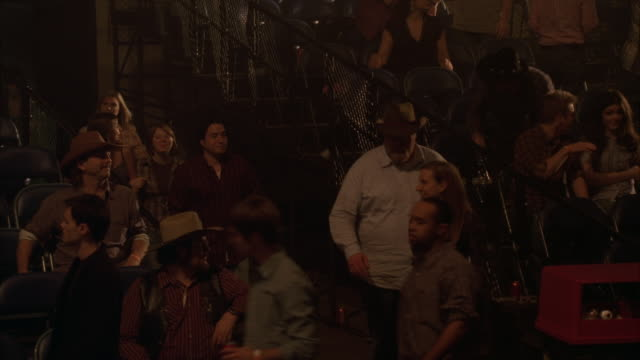 medium angle of people sitting and standing in concert venue. people wear cowboy hats and western shirts. could be country music concert. spectators. - country music stock videos and b-roll footage