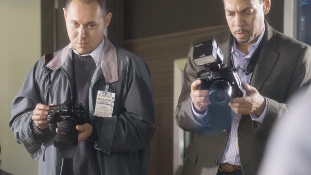 vídeos de stock e filmes b-roll de medium angle of photographers taking pictures. could be press junket or photoshoot. - emprego na comunicação social