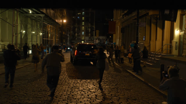 vidéos et rushes de medium angle of photographers taking pictures of black suv limo. could be paparazzi. scaffoling on buildings. cobblestone streets. could be event. - journalist