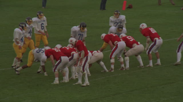 medium angle of point after attempt during high school football game. see team on offense dressed in red and white uniforms. see defensive team in yellow and blue uniforms. see teams line up and kicker kick football.
