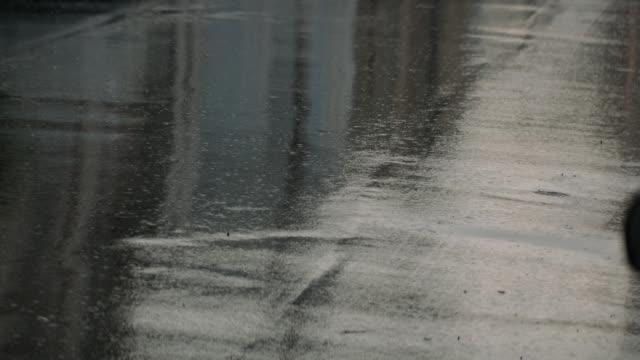 medium angle of rain falling on city street.