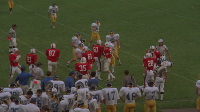 medium angle of running play at high school football game.  see defensive  team  dressed in red and white uniforms. see offensive team dressed in yellow and blue uniforms. see running back in yellow receive football from quarterback and run ball to left a