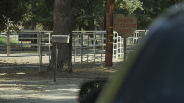 medium angle of sign on side of road. horses in corral.