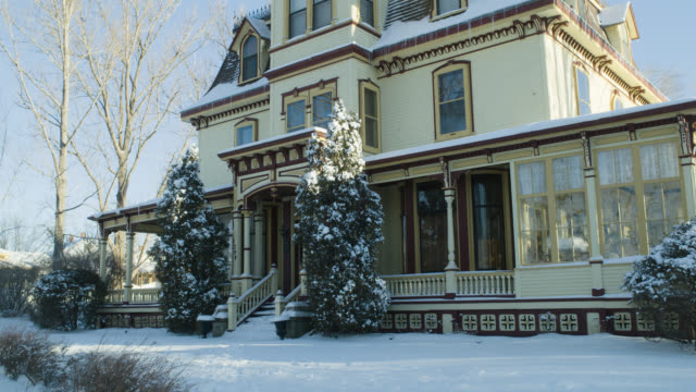 medium angle of snow covered multi-story victorian house. trees and branches visible.