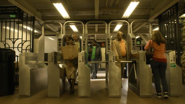 medium angle of subway station entrance. commuters enter and exit through turnstiles. - okänt kön bildbanksvideor och videomaterial från bakom kulisserna