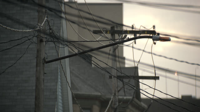 medium angle of telephone pole and wires. - telegraph pole stock videos and b-roll footage