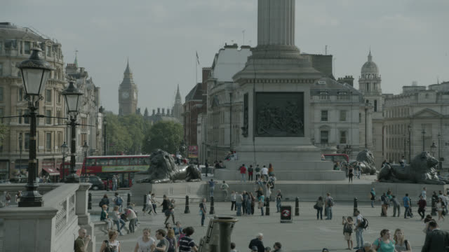 medium angle of trafalgar square. pedestrians, tourists, city streets, and nelson column partialyl visible. big ben visible in bg. - 角度点の映像素材/bロール