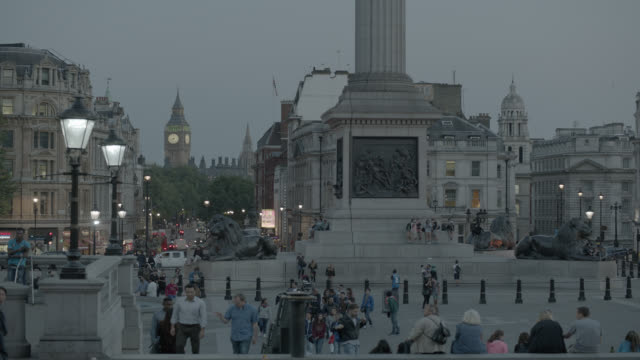 medium angle of trafalgar square. pedestrians, tourists, nelson column, and city streets visible. big ben in bg. - colonna architettonica video stock e b–roll