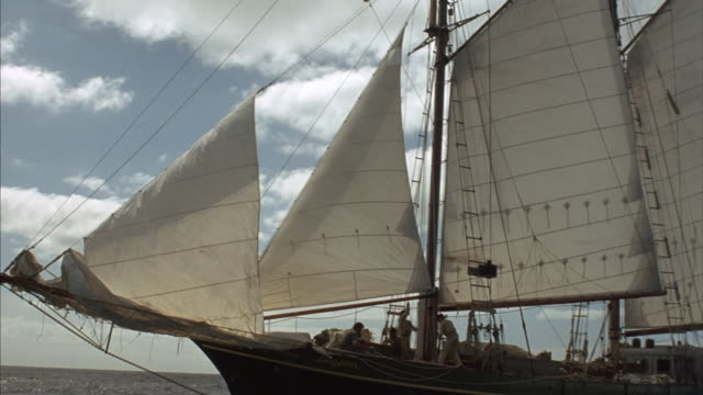 medium angle of wooden ship sailing on ocean waves. see three men on ship, one pulls up the sail. camera pans from right to left, passing in front of ship to other side. - nave a vela video stock e b–roll