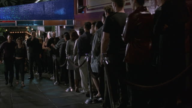 Medium angle. people waiting in line to get into nightclub. bouncers at front of line. people walking by on sidewalk.