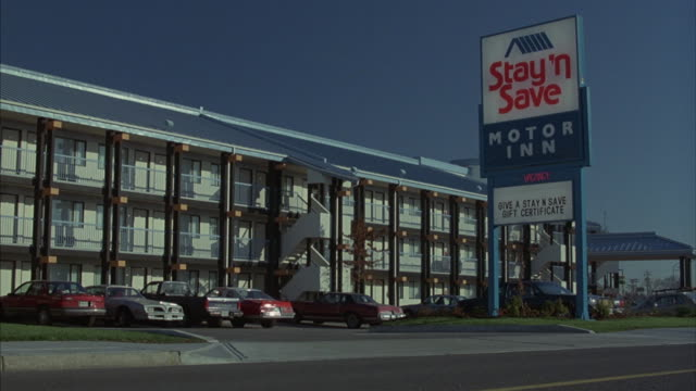 medium angle pov low in street of three story hotel or inn. - motel stock videos and b-roll footage