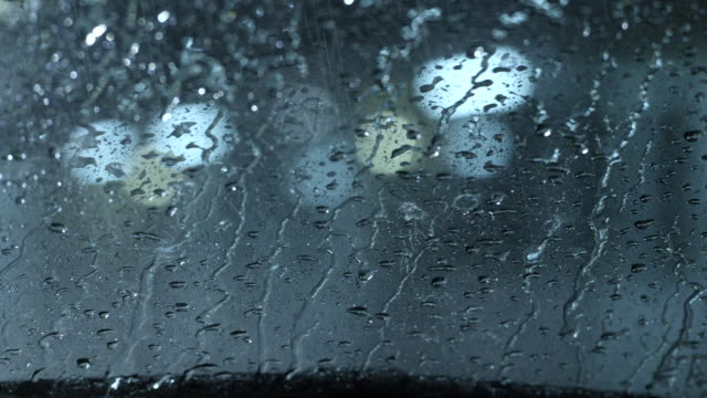 medium angle pov through windshield of car in parking lot or motel. rain, windshield wipers.
