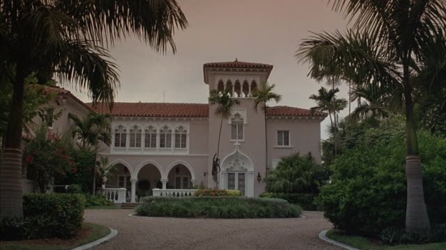 Medium angle red tile roof two story mansion. could be spanish stucco style mansion. pink exterior with white arched porch entrance and circular drive with central sculpture. mansion has lookout tower that extends over roof.