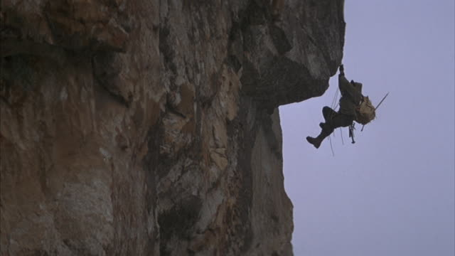 Medium angle stunt of mountain climber hanging from rope on side of mountain. see climber attempt to climb up mountainside and slip. see climber hang from rope and attempt to climb up. see snow fall.