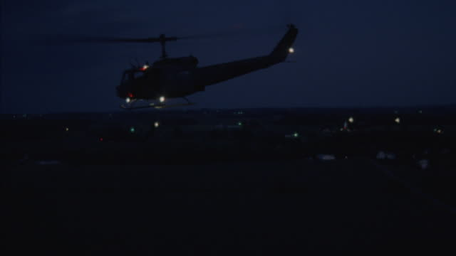 medium angle tracking shot of three black hawk or military helicopters flying across field to left. see dense trees in foreground and horizon in far background. search light reflects on trees. - military helicopter stock videos & royalty-free footage