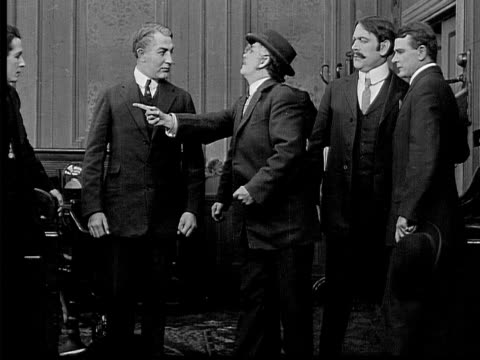 vidéos et rushes de 1909 b/w medium businessmen happily shaking hands in office/ man entering and talking to boss/ boss threatening man/ man leaving - féliciter