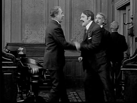 stockvideo's en b-roll-footage met 1909 b/w medium businessmen talking in office as boss arrives/ shaking boss's hand/ other men arrive looking happy - 1900 1909