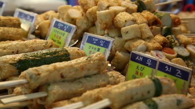 medium close and wide view of vendor cutting up fried rolls to place on a skewer on a cart along namdaemun market in seoul, south korea, close pull... - skewer stock videos & royalty-free footage