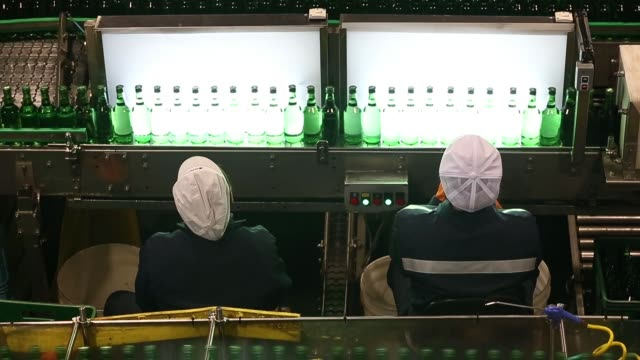 stockvideo's en b-roll-footage met medium close pull focus of bottles moving along conveyor overhead medium view of employees inspecting bottles moving along conveyor medium side view... - middelenmisbruik