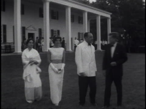 medium close shot of jacqueline kennedy standing outdoors in between ayub khan and his wife. all are wearing fancy attire. halfway through this shot... - jackie kennedy stock videos & royalty-free footage