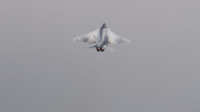 medium close shot of us f-18 hornet military jet accelerating away from camera, afterburner exhaust glows orange hot. - afterburner stock videos and b-roll footage