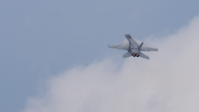 medium close shot of us f-18 hornet military jet barrel-rolls away from camera, afterburner exhaust glows orange. - afterburner stock videos and b-roll footage