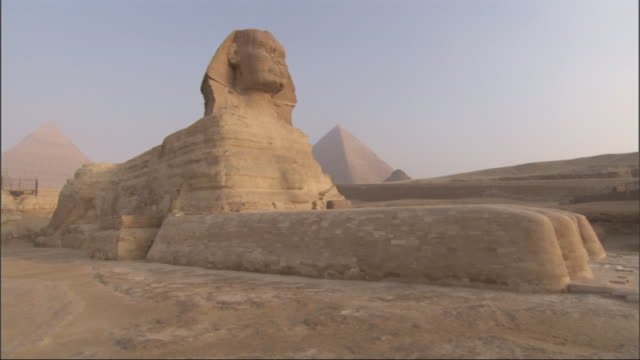 Medium Close Up, crane - The Great Sphinx sits in front of the Great Pyramids / Egypt