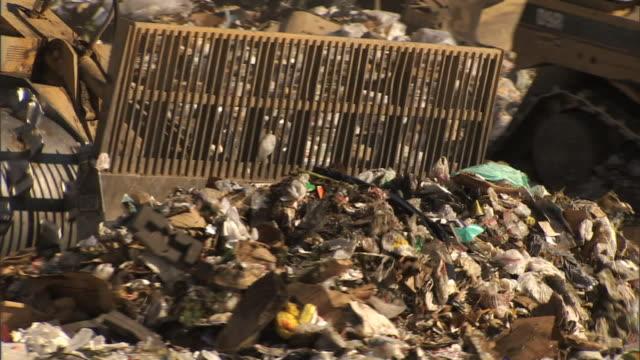 medium close up hand-held - a bulldozer pushes trash around a landfill / bakersfield, california - veicolo per costruzioni video stock e b–roll