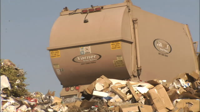 medium close up hand-held - a garbage truck dumps trash at a landfill / bakersfield, california - garbage truck stock videos and b-roll footage