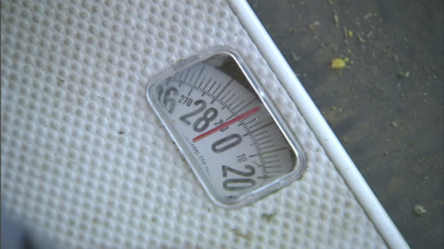 medium close up hand-held - a man steps onto a scale, and it reads 220 pounds. / california, usa - 体重計点の映像素材/bロール