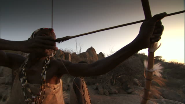 vidéos et rushes de medium close up hand-held - a tribesman shoots an arrow from a bow as another man watches. / hadza, united republic of tanzania - culture indigène