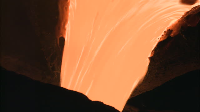 Medium Close Up hand-held - Molten metal pours from one container into another /  Ohio, United States