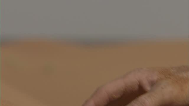 Medium Close Up hand-held - Sand sifts through fingers / Sahara, Egypt