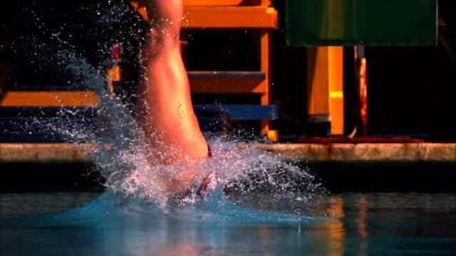 medium close up, locked down - a diver dives into a pool / usa - 水に飛び込む点の映像素材/bロール