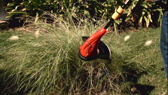 Medium Close Up, Locked Down - A string trimmer cuts long grass in slow motion / USA