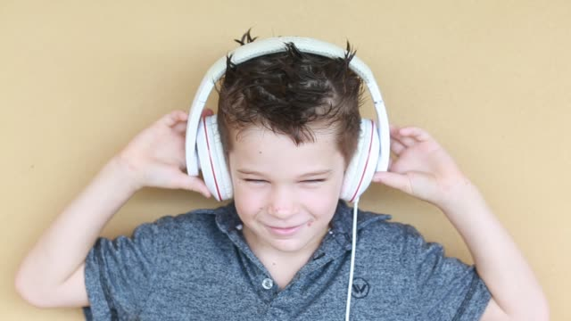 medium close up of 6 year old boy moving to music he is listening to on the headphones - kelly mason videos 個影片檔及 b 捲影像